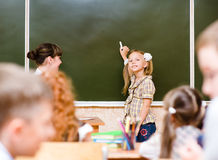 Schoolgirl answers questions of teachers near a school board.  Royalty Free Stock Photo