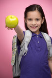 Schoolgirl with apple. Cheerful little schoolgirl holding an app Stock Photo