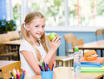 Schoolgirl with apple while having lunch stock image