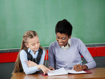 Schoolgirl Asking Question To Teacher At Desk Royalty Free Stock Images