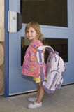 Schoolgirl with backpack. Smiling young schoolgirl with backpack stood in front of door Royalty Free Stock Photography