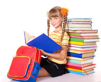 Schoolgirl with backpack reading pile of books. Royalty Free Stock Photography