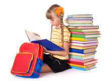 Schoolgirl with backpack reading pile of books. Stock Photo