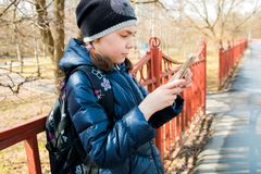Schoolgirl with backpack in warm sunny weather stands at the fence and looks at the phone stock photos