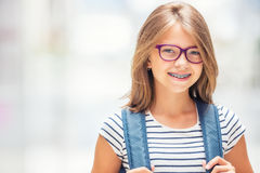 Schoolgirl with bag, backpack. Portrait of modern happy teen school girl with bag backpack. Girl with dental braces and glasses Stock Photos