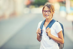 Schoolgirl with bag, backpack. Portrait of modern happy teen school girl with bag backpack. Girl with dental braces and glasses