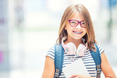 Schoolgirl with bag, backpack. Portrait of modern happy teen school girl with bag backpack headphones and tablet. Girl with dental braces and glasses royalty free stock photo