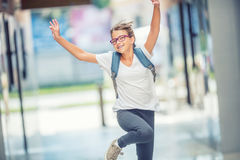Schoolgirl with bag, backpack. Portrait of modern happy teen school girl with bag backpack. Girl with dental braces and glasses.  Royalty Free Stock Photos