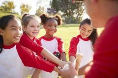 Schoolgirl baseball team in a team huddle with their coach stock photos