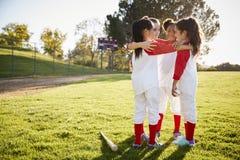 Schoolgirl baseball team talking in team huddle before game stock images