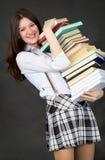 Schoolgirl bearing pile of books Royalty Free Stock Photo