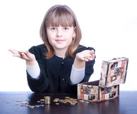 Schoolgirl. Beautiful girl in a school uniform sitting at a table and counts coins, the box stands on the table Royalty Free Stock Photo