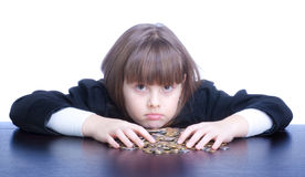 Schoolgirl. Beautiful girl in a school uniform sitting at a table and counts coins. She confused Royalty Free Stock Photography