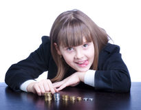 Schoolgirl. Beautiful girl in a school uniform sitting at a table and counts coins, she makes a face Stock Photography
