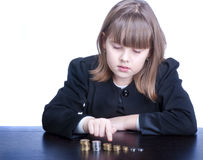 Schoolgirl. Beautiful girl in a school uniform sitting at a table and counts coins, she points by finger Stock Image