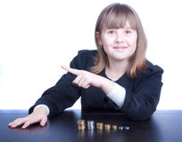Schoolgirl. Beautiful girl in a school uniform sitting at a table and counts coins, she shows finger up Royalty Free Stock Photos