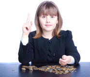 Schoolgirl. Beautiful girl in a school uniform sitting at a table and counts coins, shows an idea Stock Photography