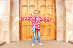 Schoolgirl before big wooden door Royalty Free Stock Image