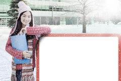 Schoolgirl with billboard and winter clothes Stock Photography