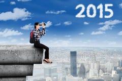 Schoolgirl with binoculars looking at number 2015 Royalty Free Stock Images