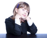 Schoolgirl. In black-and-white uniform sitting at a table with a purple pencil behind her ear. Thoughtful girl Stock Photos