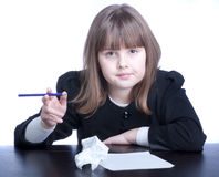 Schoolgirl. In black-and-white uniform sitting at a table with a purple pencil in hand. Before her sheet of paper and crumpled paper. Thoughtful girl solves the Royalty Free Stock Photo