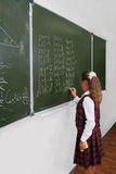 Schoolgirl at the blackboard. Stock Photos