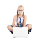 Schoolgirl wearing a school uniform sitting on the floor with a laptop on your lap Stock Images