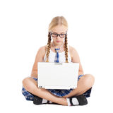 Schoolgirl wearing a school uniform sitting on the floor with a laptop on your lap Stock Photo