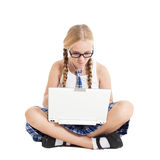 Schoolgirl wearing a school uniform sitting on the floor with a laptop on your lap Stock Photos