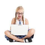 Schoolgirl wearing a school uniform sitting on the floor with a laptop on your lap Royalty Free Stock Image