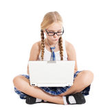 Schoolgirl wearing a school uniform sitting on the floor with a laptop on your lap Royalty Free Stock Images