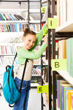 Schoolgirl with blue bag searching books. And holding exercise books on the bookshelf in library stock image
