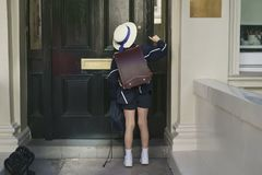Schoolgirl in blue suit, hat and white sneakers. Came back from school and knocks on the door Stock Photo