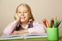 Schoolgirl with a book. A child learns at home Stock Photography