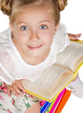 Schoolgirl with book sitting on heap of books Royalty Free Stock Photos