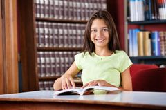 Schoolgirl With Book Sitting At Table In Library Royalty Free Stock Images
