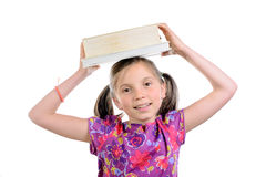 Schoolgirl with books on her head Royalty Free Stock Photo