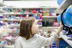 Schoolgirl buying globe for school at store. First grader choosing globe in store for school stock photos