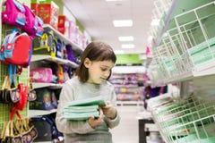 Schoolgirl buying notebooks. Schoolgirl choosing office supplies in shop stock image