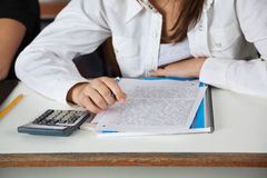 Schoolgirl With Calculator; Paper And Book At Desk Stock Images