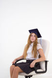 Schoolgirl with cap graduate sit on chair, thinking about future Royalty Free Stock Photo