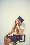 Schoolgirl with cap graduate sit on chair, thinking about future Stock Photos