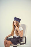 Schoolgirl with cap graduate sit on chair, thinking about future Royalty Free Stock Image