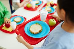 School food. Schoolgirl carrying red plastic tray with sandwich on plate, glass of drink and green apple during lunch break Royalty Free Stock Photos