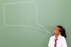 Schoolgirl chat box. Primary schoolgirl looking at chat box drawn on blackboard Stock Image