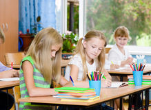 Schoolgirl cheating at exam, looking at a friend's writing Royalty Free Stock Images