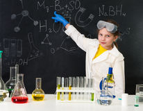 Schoolgirl in chemistry lab pointing at formula on blackboard Royalty Free Stock Photos