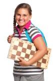 Schoolgirl with chessboard Stock Images