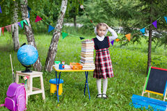 Schoolgirl child kid girl holding a huge pack of books with her. Hand above head, classroom outdoors, difficulty of studying Royalty Free Stock Images